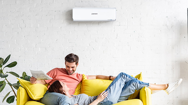 young couple sitting on lounge underneath heat pump
