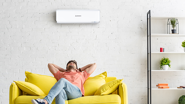 man sitting on couch underneath mitsubishi heavy industries heat pump after setting timer