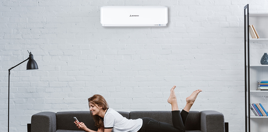 5 reasons to choose mhi header. lady lying on couch underneath heat pump