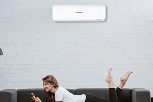 woman on couch underneath mitsubishi heavy industries split system heat pump